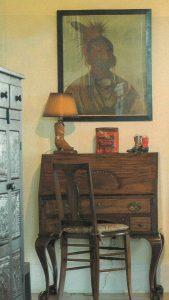 Western art hanging above an antique desk.