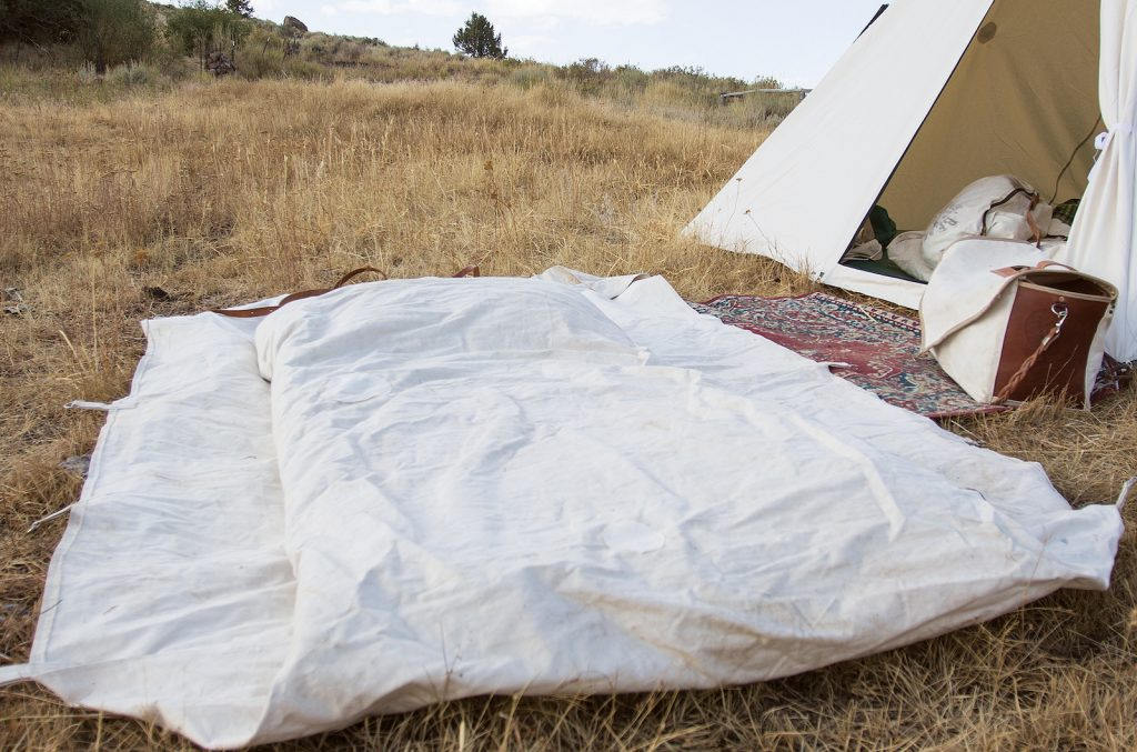 A cowboy's bedroll with the tarp tucked in on the sides.
