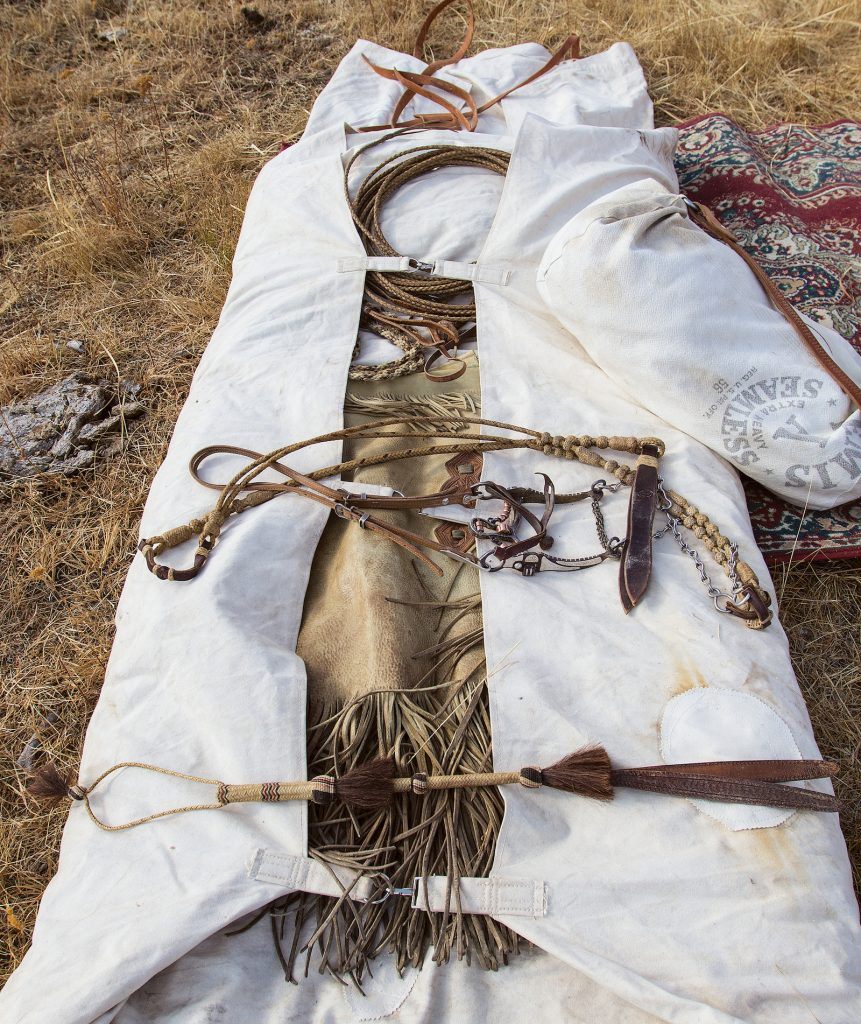 A bedroll with gear laid inside of it.