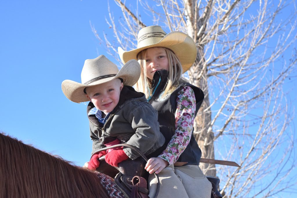 Young cowgirl Grace Young rides with her little brother.